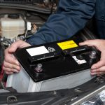 person installing car battery
