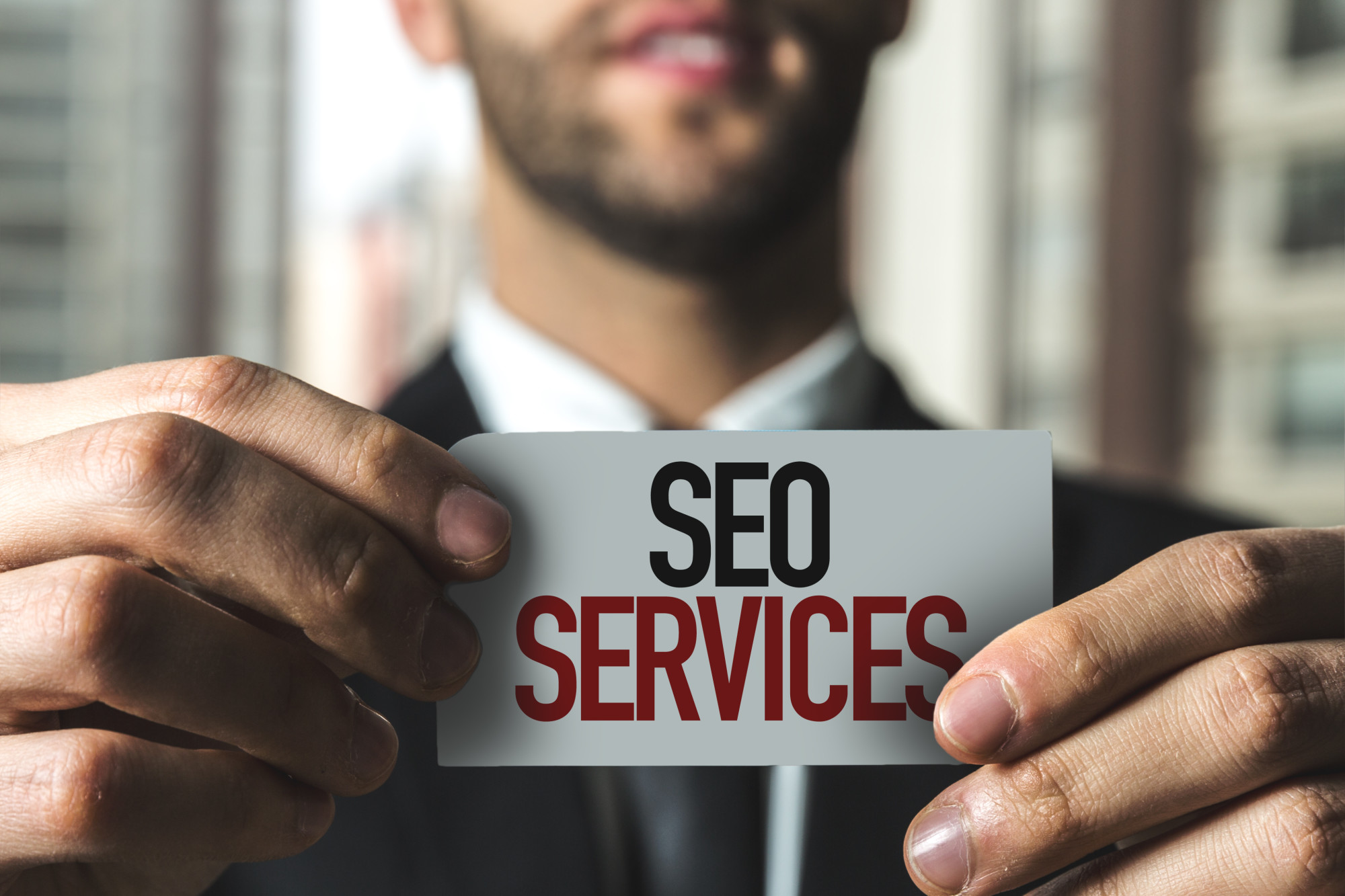 man holding seo services card