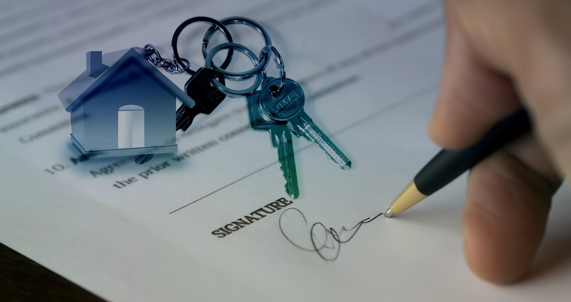 house keychain and person signing document